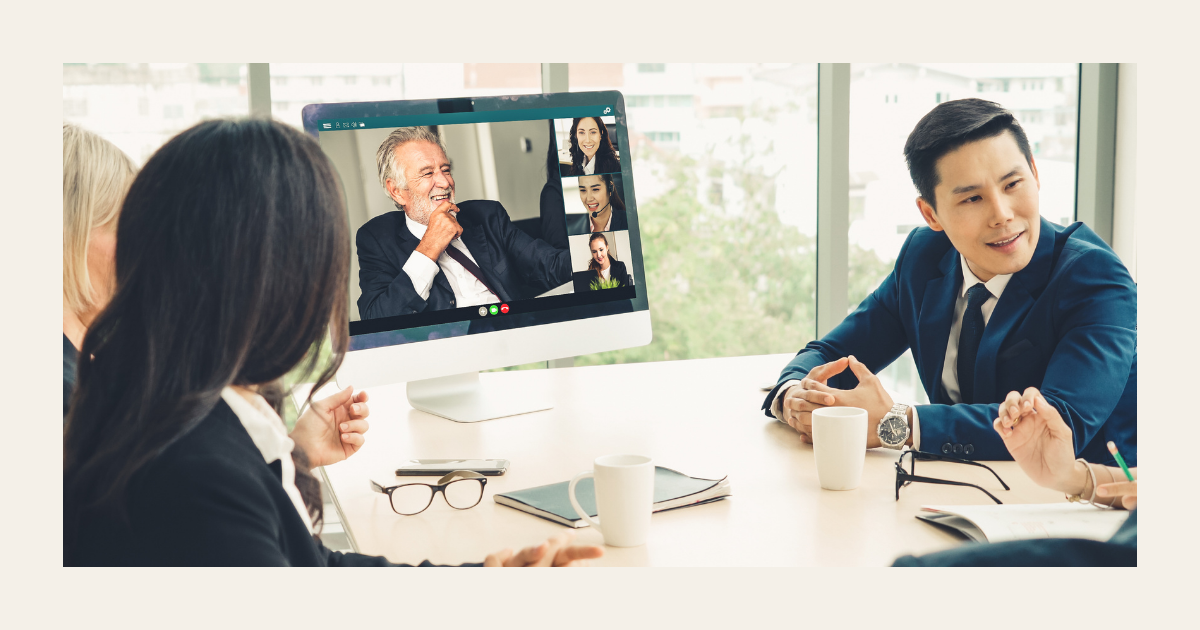 Four people are gathered at a table for a business meeting. There is a computer monitor set up featuring the images of four additional remote employees attending the meeting.